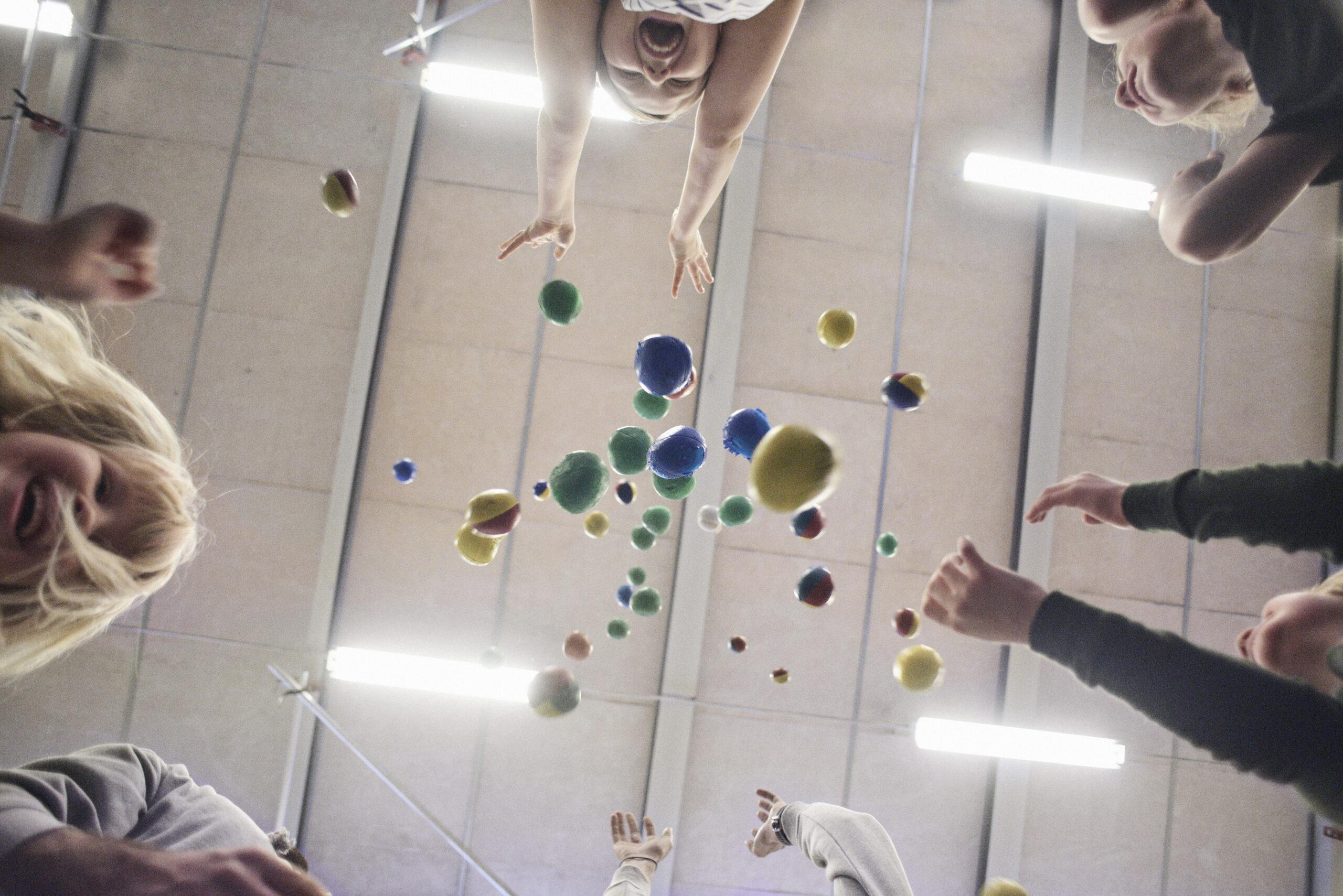 Bild tagen underifrån på barn med jongleringsbollar