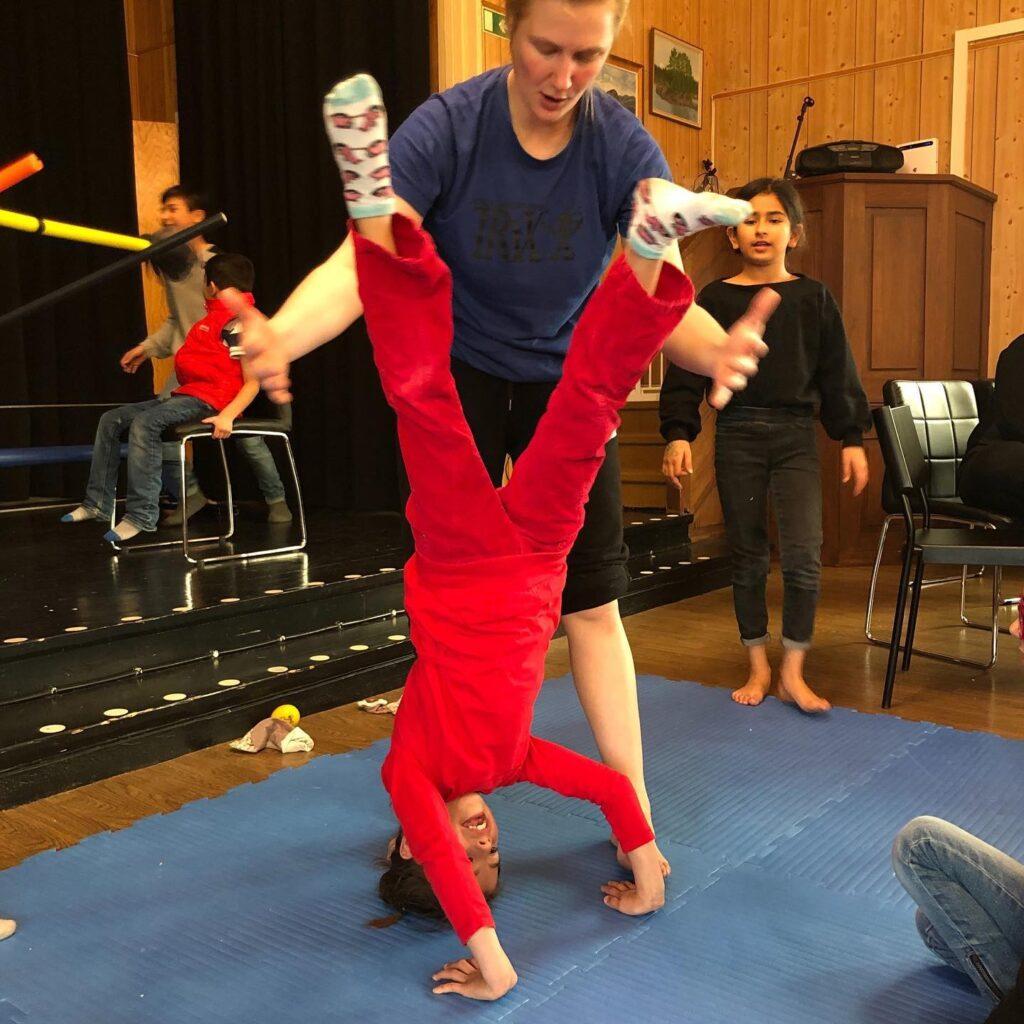 Cirkusskola. Sofia hjälper barn att stå på huvudet
